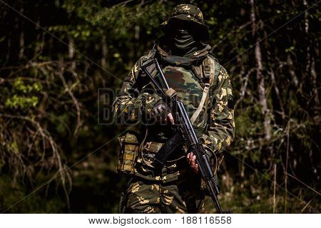 Photo of military man with gun in woods during day