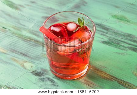 Summer refreshing cocktail with strawberry, ice and thyme on a light green wooden table