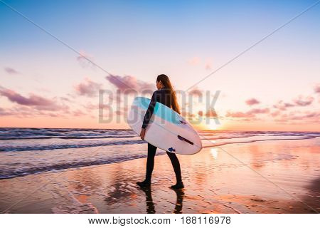 Surf girl with surfboard at sunset or sunrise and ocean.
