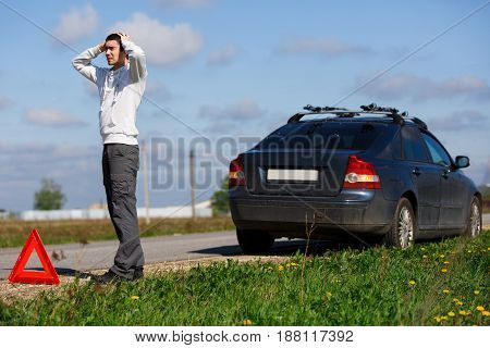 Brunet stands on road near broken car in afternoon