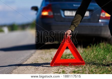 Driver puts red warning triangle on road against background of car