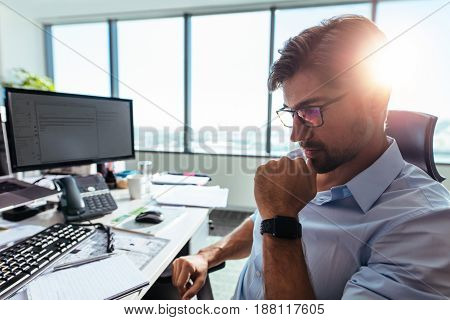 Close up of businessman wearing spectacles sitting in pensive mood with hand to his chin. Young entrepreneur sitting at his work station looking down at his desk.
