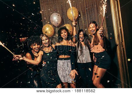 Shot of group of girls in the nightclub having a great time. Group of female friends partying in pub.