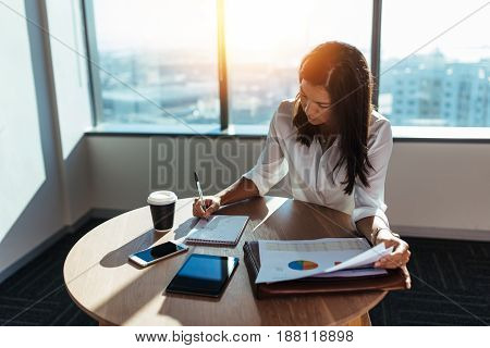 Young woman entrepreneur making business working at coffee table in office. Female business executive making business plans with a coffee cup on her table.