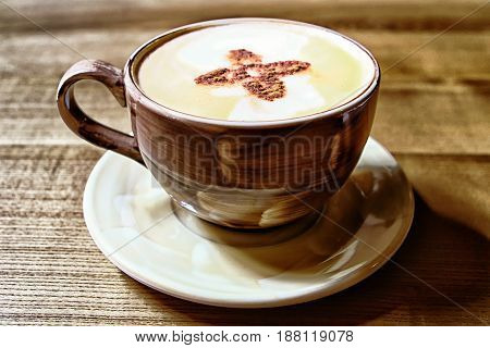 Brown hot coffee cup with flower pattern on coffee surface