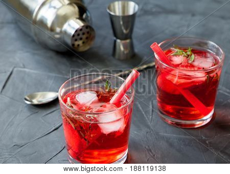 Red drink with ice. Cocktail making bar tools, strawberry and thyme leaves on a concrete background