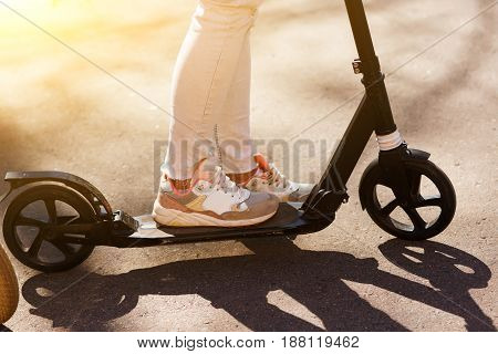 Legs on scooter. Girl in jeans on vacation in park during day. sun glare