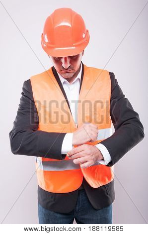 Contractor Wearing Hardhat And Reflective Vest Arranging His Shirt