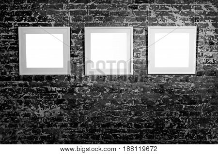 Three empty frames on black brick wall. Blank space posters or art frame waiting to be filled. Square Black Frame Mock-Up.