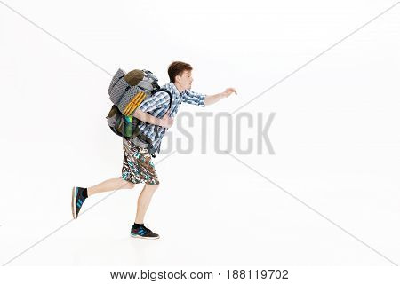 Young tourist with a backpack running on a white background. hiker was late