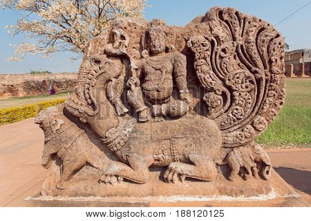 Ancient Hindu god sitting on myth lion creature ruins of stone relief carvings from the 7th century temple's wall, Aihole town, of Karnataka. Old Indian artwork