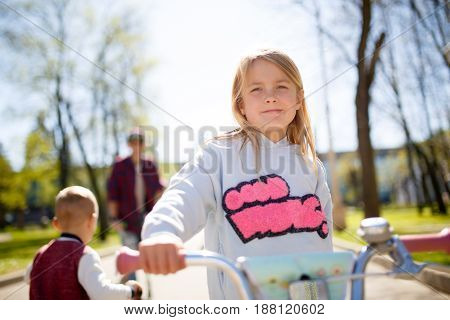 Photo of girl on bike for walk with family in park