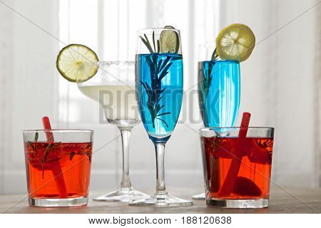 Different cocktails in front of window. set