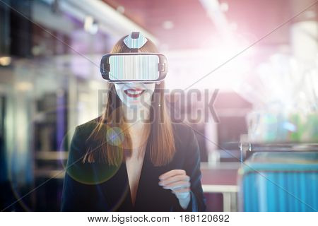 Smiling female wearing virtual reality glasses on party background.
