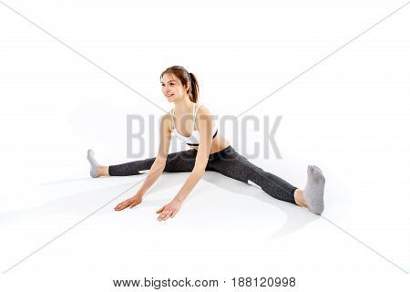 Sporty woman sitting on twine on empty white background