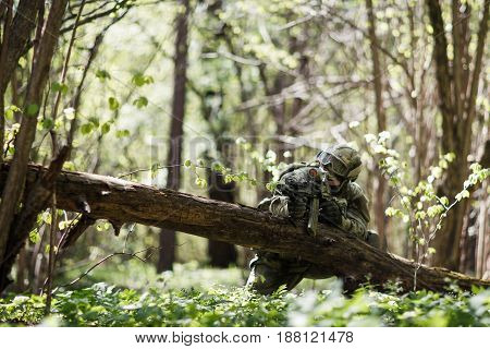 Scout with weapons in forest during day on assignment