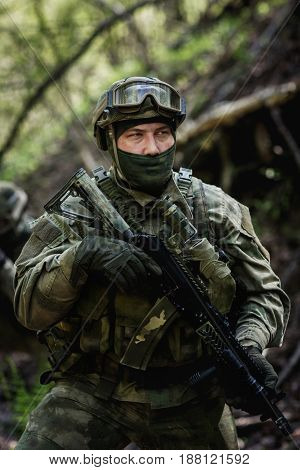 Photo of soldier in camouflage and in submachine gun at forest