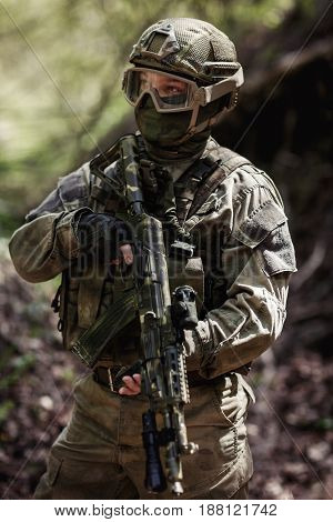 Photo of soldier with gun in woods during day