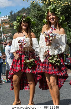 ESTREITO DE CAMARA DE LOBOS PORTUGAL - SEPTEMBER 10 2016: Women wearing in colorful costumes at Madeira Wine Festival in Estreito de Camara de Lobos Madeira Portugal. The Madeira Wine Festival honors the grape harvest with a celebration of traditional loc