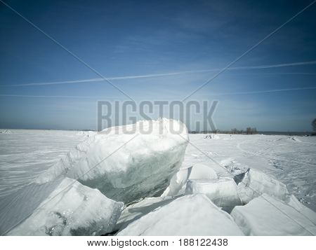 Beach in winter in Siberia. Ice breaks on the surface. In the distance on the horizon the shore and the city