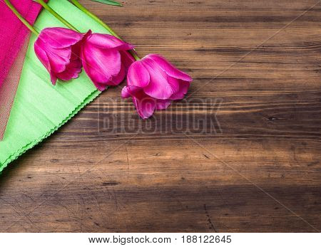 Pink tulips, floral arrangement on wooden background with green paper and space for message. Background for Mother's Day, 8 March and other greeting cards or invitations for lovely women. Soft focus.