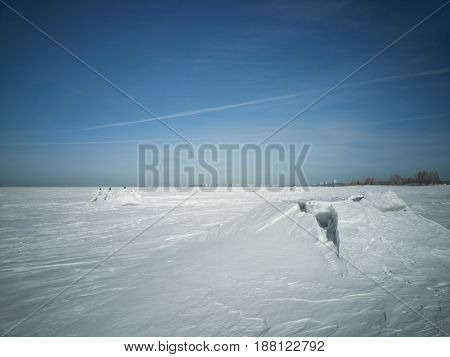 Beach in winter in Siberia. Ice breaks on the surface. In the distance on the horizon walking people the shore and the city