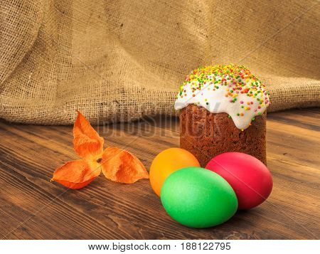 Easter cake and easter colored egg with dry flower. Russian and Ukrainian, orthodox, slavic traditional Easter kulich on rural background from old wood and burlap. Selective focus.