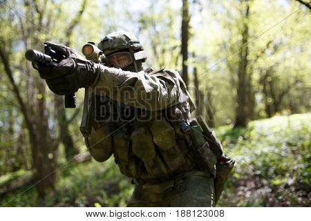 Soldier with weapons in military intelligence at woods during day