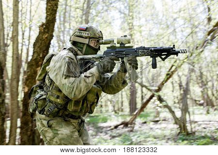 Soldier takes aim in forest with submachine gun