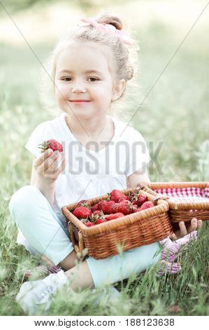 Smiling baby girl 4-5 year old eating tasty strawberry outdoors. Looking at camera. Summer time.