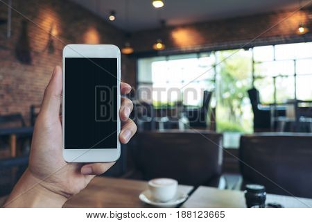 Mockup image of hand holding white mobile phone with blank black screen in modern cafe