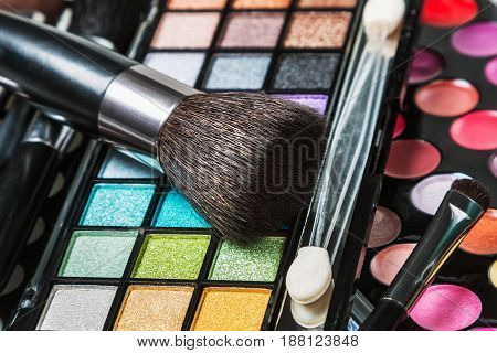 Brushes and pallets for make-up. Focus on the brush in the center of the frame