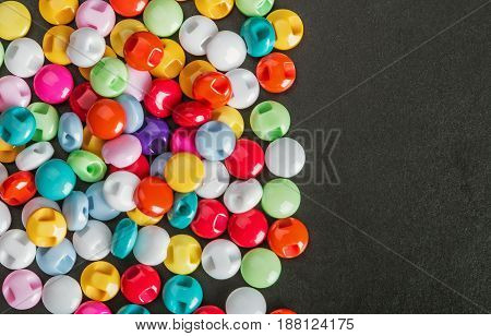 Multi colored buttons on a black background. Place on chsernom background can be used for text. Focus on a black background