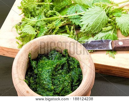 cooked and raw nettles on a wooden board and in a rustic mortar