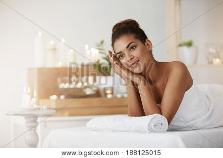 Dreamy beautiful girl in towel smiling resting in spa salon.