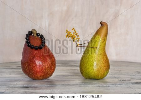 Red and yellow pear on a wooden table. Two lovers pear. Composition of pears.
