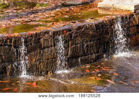 Little waterfall with the stonework on the creek with dry leaves in sunny autumn day