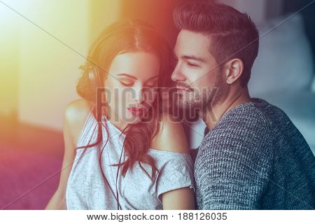 Young couple listening music by headphones together at home in sunset sharing music