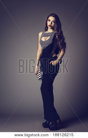 Fashionable woman wearing sexy top and stylish trousers and holding handbag. Fashion style studio portrait of young beautiful woman with long curly hair.