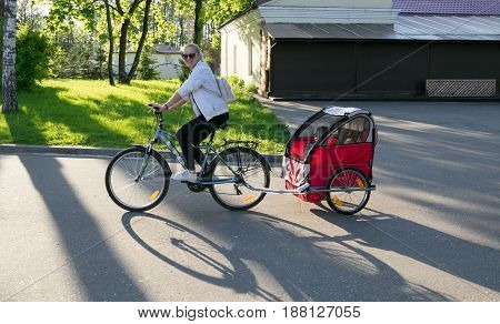 Nesvizh, Belarus - May 20, 2017: People Ride A Bicycle With A Trailer For A Child.