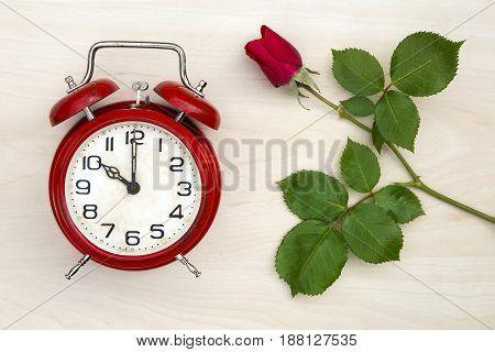 Love concept - red rose and a retro alarm clock