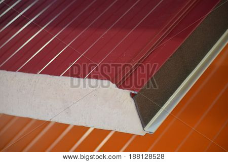 cross section of metal roof panels in different colours, insulated with styrofoam - polystyrene foam