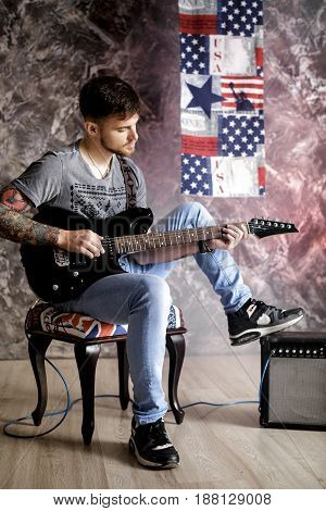 Young handsome musician playing electric guitar on a dark background
