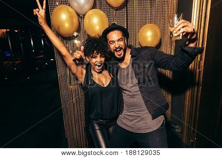 Couple smiling and dancing having fun during disco party. Happy man and woman enjoying party at nightclub.