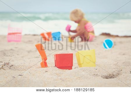 kids toys and little girl playing on tropical beach