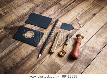 Blank stationery elements on vintage wooden table background.