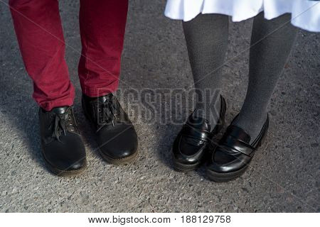 Love story told by boots. Human feet close up. Man and woman in elegand shoes. Girl in black shoes. Guy in black shoes and leather. Lady and gentleman couple in summer. Legs close up.