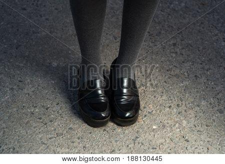 Retro Style Image Of School or student Girl's Feet In Uniform. black elegant shoes