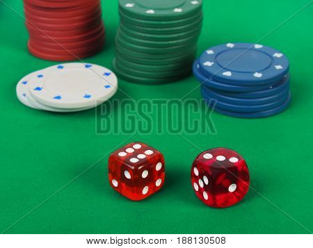 Dice and casino tokens on green table