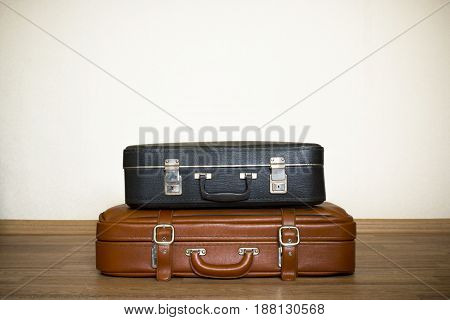 Two old leather black and brown suitcases in retro stile. Vintage accessories for business.  Travel bag for summer vacations. The handle of a suitcase